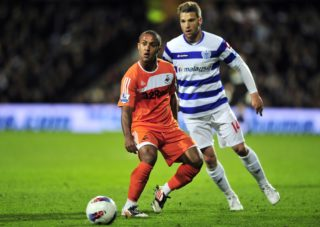 """Swansea's English midfielder Wayne Routledge (L) vies with Queens Park Rangers' Hungarian midfielder Akos Buzsaky (R) during the English Premier League football match between Queens Park Rangers and Swansea City at Loftus Road in London, England on April 11, 2012. AFP PHOTO/GLYN KIRK  RESTRICTED TO EDITORIAL USE. No use with unauthorized audio, video, data, fixture lists, club/league logos or """"live"""" services. Online in-match use limited to 45 images, no video emulation. No use in betting, games or single club/league/player publications / AFP PHOTO / GLYN KIRK"""