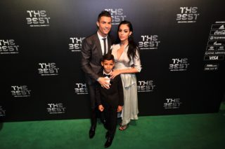 Real Madrid and Portugal forward Cristiano Ronaldo (L) poses for a photograph with partner Georgina Rodriguez (R) and his son Cristiano Ronaldo Jr as he arrives for The Best FIFA Football Awards ceremony, on October 23, 2017 in London. / AFP PHOTO / Glyn KIRK