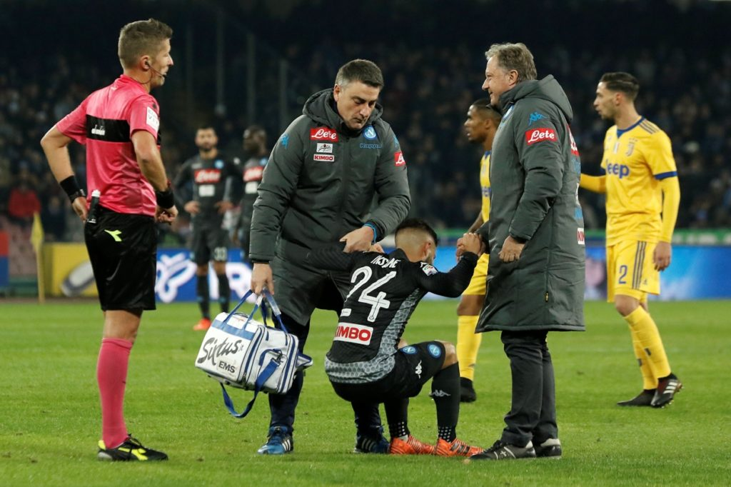 Napoli's midfielder from Italy Lorenzo Insigne (C) is helped to get up during the Italian Serie A football match Napoli vs Juventus on December 1, 2017 at the San Paolo stadium in Naples. Juventus won 0-1. / AFP PHOTO / CARLO HERMANN