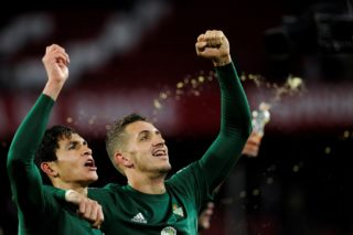 Real Betis' Moroccan defender Zou Feddal (R) celebrates with Real Betis' Algerian defender Aissa Mandi (L) after winning the Spanish league football match between Sevilla and Real Betis at the Sanchez Pizjuan stadium in Sevilla on January 6, 2018. / AFP PHOTO / CRISTINA QUICLER