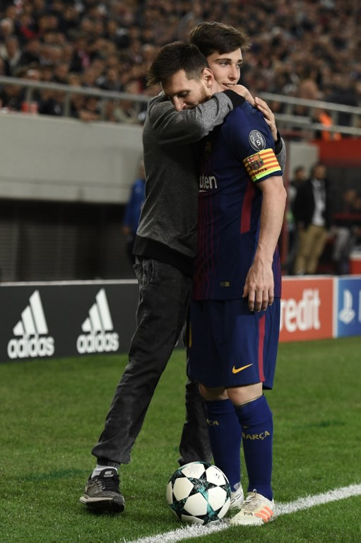 A fan arrives hugs Barcelona's Argentinian forward Lionel Messi on the pitch during the UEFA Champions League group D football match between FC Barcelona and Olympiakos FC at the Karaiskakis stadium in Piraeus near Athens on October 31, 2017.  / AFP PHOTO / ARIS MESSINIS
