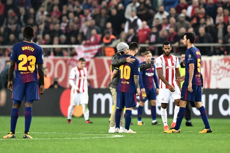 A fan who invaded the pitch takes a selfie picture with Barcelona's Argentinian forward Lionel Messi during the UEFA Champions League group D football match between FC Barcelona and Olympiakos FC at the Karaiskakis stadium in Piraeus near Athens on October 31, 2017.  / AFP PHOTO / ARIS MESSINIS