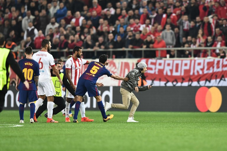 A fan who invaded the pitch, runs away with his mobile phone, during the UEFA Champions League group D football match between FC Barcelona and Olympiakos FC at the Karaiskakis stadium in Piraeus near Athens on October 31, 2017.  / AFP PHOTO / ARIS MESSINIS