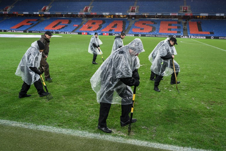 Stadium staff dig the pitch with spades under pouring rain ahead of the FIFA 2018 World Cup play-off second leg qualifiying football match between Switzerland and Northern Ireland at St Jakob-Park Stadium on November 12, 2017. / AFP PHOTO / Fabrice COFFRINI