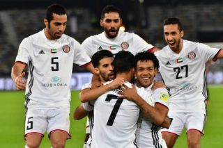 Al-Jazira's Emirati forward Ali Mabkhout (C, front) embraces his teammates Moroccan Mbark Boussoufa (C-L, behind) and Brazillian Romarinho (C-R, behind), as they celebrate after him scoring a goal against Urawa Reds during their FIFA Club World Cup quarter-final match at Zayed Sports City Stadium in the Emirati capital Abu Dhabi on December 9, 2017. / AFP PHOTO / GIUSEPPE CACACE