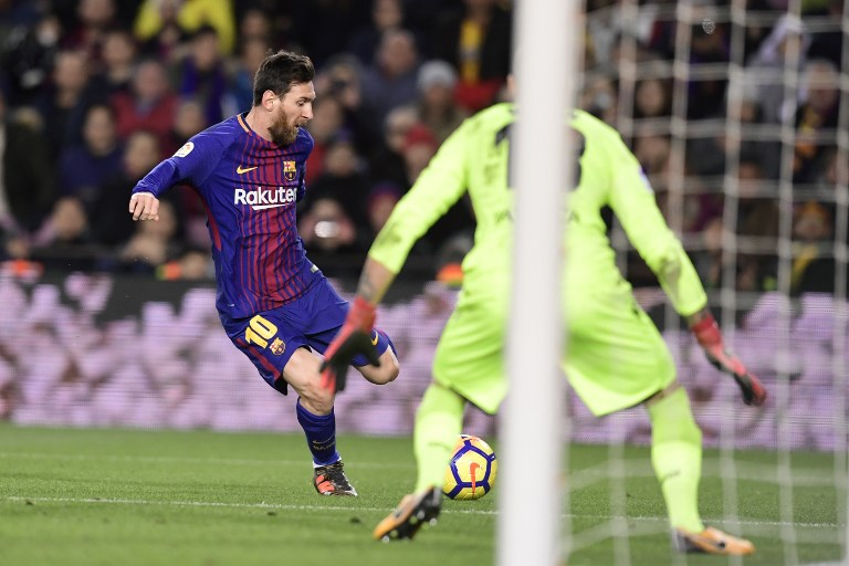 Barcelona's Argentinian forward Lionel Messi (L) kicks the ball in front of Deportivo La Coruna's Spanish goalkeeper Ruben during the Spanish league football match FC Barcelona against RC Deportivo de la Coruna at the Camp Nou stadium in Barcelona on December 17, 2017. / AFP PHOTO / JAVIER SORIANO