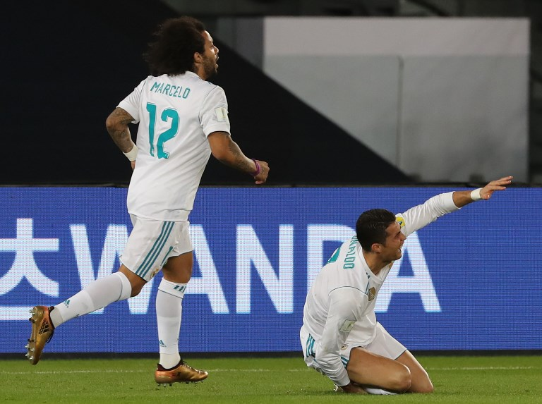 Real Madrid's Cristiano Ronaldo (R) reacts on the ground next to his teammate Marcelo during the Club World Cup UAE 2017 final football match between Gremio FBPA and Real Madrid at the Zayed Sports City Stadium in Abu Dhabi on December 16, 2017. / AFP PHOTO / KARIM SAHIB