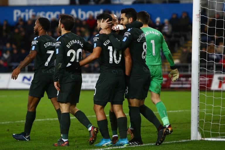 Manchester City's Argentinian striker Sergio Aguero (C) celebrates with teammates after scoring their fourth goal during the English Premier League football match between Swansea City and Manchester City at The Liberty Stadium in Swansea, south Wales on December 13, 2017. / AFP PHOTO / Geoff CADDICK / RESTRICTED TO EDITORIAL USE. No use with unauthorized audio, video, data, fixture lists, club/league logos or 'live' services. Online in-match use limited to 75 images, no video emulation. No use in betting, games or single club/league/player publications.  /