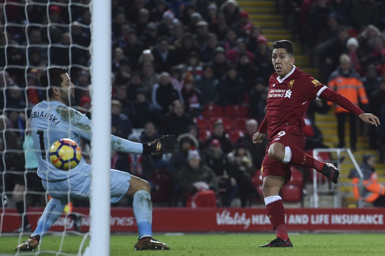 Liverpool's Brazilian midfielder Roberto Firmino (R) volleys the ball from a cross to score their second goal during the English Premier League football match between Liverpool and Swansea City at Anfield in Liverpool, north west England on December 26, 2017. / AFP PHOTO / PAUL ELLIS / RESTRICTED TO EDITORIAL USE. No use with unauthorized audio, video, data, fixture lists, club/league logos or 'live' services. Online in-match use limited to 75 images, no video emulation. No use in betting, games or single club/league/player publications.  /