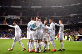 Real Madrid's Welsh forward Gareth Bale (C) celebrates a goal with teammates during the Spanish league football match Real Madrid CF against Getafe CF at the Santiago Bernabeu stadium in Madrid on March 3, 2018. / AFP PHOTO / PIERRE-PHILIPPE MARCOU