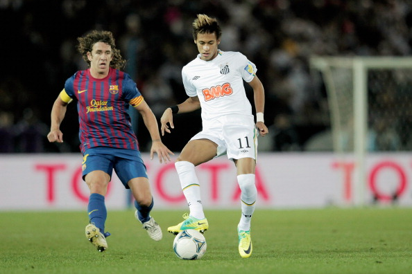 YOKOHAMA, JAPAN - DECEMBER 18:  Neymar (R) of Santos challenged by Carles Puyol of FC Barcelona during the FIFA Club World Cup Final match between Santosl and Barcelona at the Yokohama International Stadium on December 18, 2011 in Yokohama, Japan.  (Photo by Lintao Zhang/Getty Images)