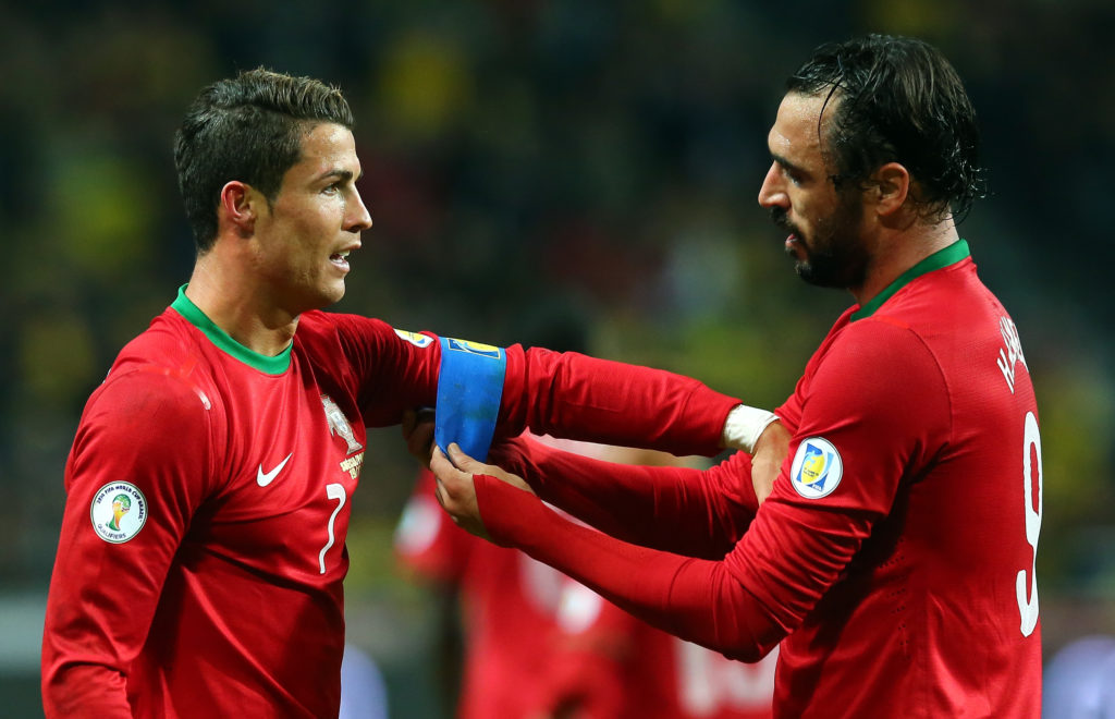 STOCKHOLM, SWEDEN - NOVEMBER 19: Huga Almeida helps Cristiano Ronaldo of Portugal with his captains bandage runs with the ball during the FIFA 2014 World Cup Qualifier Play-off Second Leg match between Sweden and Portugal at Friends Arena on November 19, 2013 in Stockholm, Sweden.  (Photo by Martin Rose/Getty Images,)