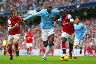 MANCHESTER, ENGLAND - DECEMBER 14:  Yaya Toure of Manchester City is closed down by Mathieu Flamini and Bacary Sagna of Arsenal  during the Barclays Premier League match between Manchester City and Arsenal at Etihad Stadium on December 14, 2013 in Manchester, England.  (Photo by Clive Brunskill/Getty Images)