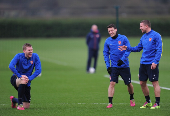 ST ALBANS, ENGLAND - FEBRUARY 18:  Per Mertesacker, Mesut Ozil and Lukas Podolski of Arsenal warm up during a training session at London Colney on February 18, 2014 in St Albans, England.  (Photo by Shaun Botterill/Getty Images)