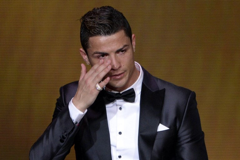 Real Madrid's Portuguese forward Cristiano Ronaldo cries after receiving the 2013 FIFA Ballon d'Or award for player of the year during the FIFA Ballon d'Or award ceremony at the Kongresshaus in Zurich on January 13, 2014. AFP PHOTO / FABRICE COFFRINI / AFP PHOTO / FABRICE COFFRINI