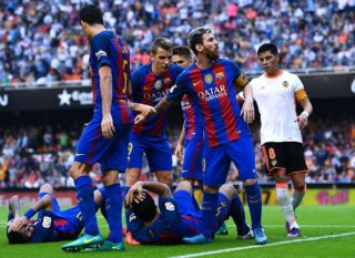 VALENCIA, SPAIN - OCTOBER 22:  Lionel Messi of FC Barcelona celebrates with his team mates as Neymar Jr. and Luis Suarez reacts on the pitch after being hit by objects thrown from the seats after scoring his team's third from the penalty spot during the La Liga match between Valencia CF and FC Barcelona at Mestalla stadium on October 22, 2016 in Valencia, Spain.  (Photo by David Ramos/Getty Images)