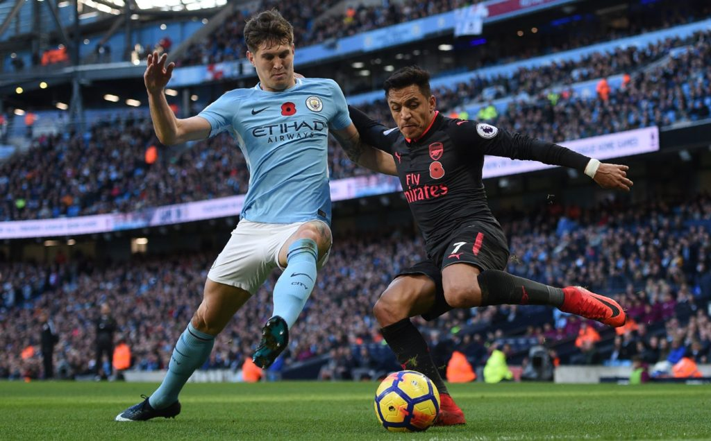 Arsenal's Chilean striker Alexis Sanchez (R) vies with Manchester City's English defender John Stones (L) during the English Premier League football match between Manchester City and Arsenal at the Etihad Stadium in Manchester, north west England, on November 5, 2017. / AFP PHOTO / Oli SCARFF / RESTRICTED TO EDITORIAL USE. No use with unauthorized audio, video, data, fixture lists, club/league logos or 'live' services. Online in-match use limited to 75 images, no video emulation. No use in betting, games or single club/league/player publications.  /