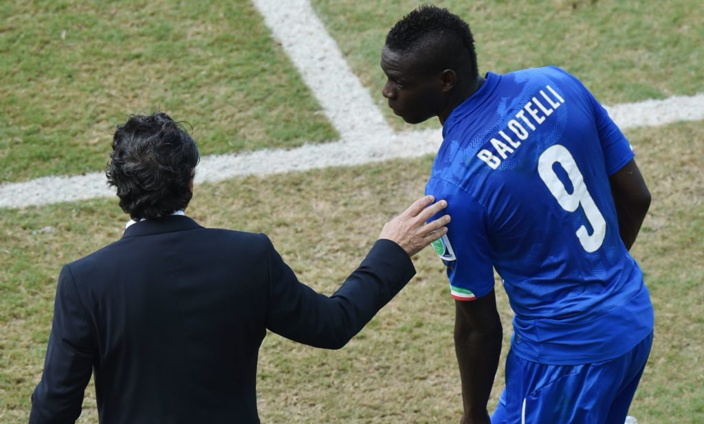Italy's forward Mario Balotelli (R) reacts past Italy's coach Cesare Prandelli after being fouled during a Group D football match between Italy and Uruguay at the Dunas Arena in Natal during the 2014 FIFA World Cup on June 24, 2014.   AFP PHOTO/ YASUYOSHI CHIBA / AFP PHOTO / YASUYOSHI CHIBA
