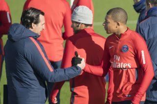 Paris Saint-Germain's Spanish head coach Unai Emery (L) shakes hand Paris Saint-Germain's French forward Kylian Mbappe during a team's training session on November 16, 2017 in Saint-Germain-en-Laye, near Paris. / AFP PHOTO / BERTRAND GUAY