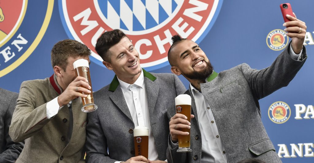 (L-R) Bayern Munich's German striker Thomas Mueller, Bayern Munich's Polish striker Robert Lewandowski and Bayern Munich's Chilian midfielder Arturo Vidal gratulate Thomas Mueller to his birthday and pose for a selfie during a photo shooting for a FC Bayern Munich sponsor in traditional bavarian clothing in Munich, southern Germany, on September 13, 2017. / AFP PHOTO / GUENTER SCHIFFMANN