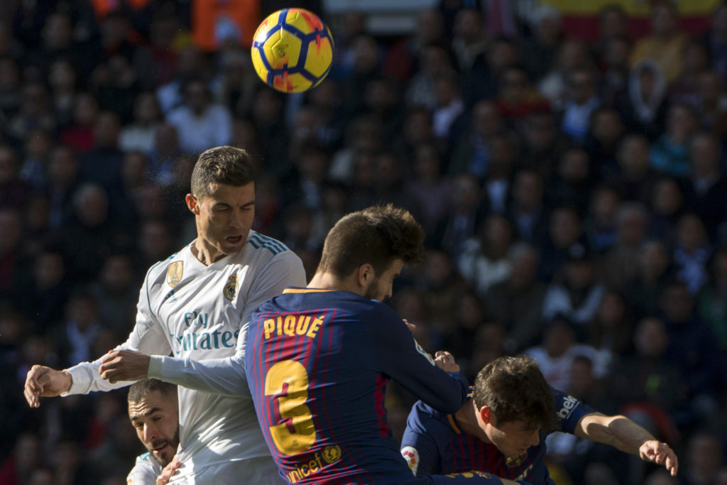 """Real Madrid's Portuguese forward Cristiano Ronaldo (L) and Barcelona's Spanish defender Gerard Pique jump for the ball during the Spanish League """"Clasico"""" football match Real Madrid CF vs FC Barcelona at the Santiago Bernabeu stadium in Madrid on December 23, 2017.  / AFP PHOTO / CURTO DE LA TORRE"""