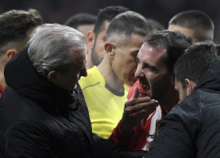 Atletico Madrid's Uruguayan defender Diego Godin (R) shows his mouth to the team's doctor after resulting injured during the Spanish league football match between Club Atletico de Madrid and Valencia CF at the Wanda Metropolitano stadium in Madrid on February 4, 2018. / AFP PHOTO / GABRIEL BOUYS