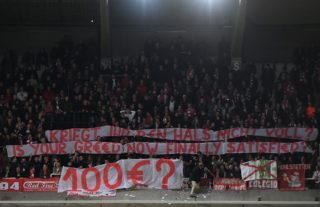 """Bayern Munich fans hold a banner reading """"100 euro, is your greed now finally satisfied?"""" during the UEFA Champions League Group B football match between Anderlecht and Bayern Munich at Constant Vanden Stock Stadium in Brussels on November 22, 2017.  / AFP PHOTO / EMMANUEL DUNAND"""