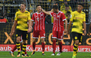 Bayern Munich's Polish striker Robert Lewandowski (2ndL) reacts after scoring during the German Supercup football match between Borussia Dortmund vs Bayern Munich in Dortmund, western Germany, on August 5, 2017. / AFP PHOTO / PATRIK STOLLARZ