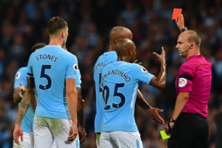 Manchester City's English defender Kyle Walker is shown the red card by referee Robert Madley (R) as Manchester City's English defender John Stones (L) and Manchester City's Brazilian midfielder Fernandinho react during the English Premier League football match between Manchester City and Everton at the Etihad Stadium in Manchester, north west England, on August 21, 2017. / AFP PHOTO / Anthony DEVLIN / RESTRICTED TO EDITORIAL USE. No use with unauthorized audio, video, data, fixture lists, club/league logos or 'live' services. Online in-match use limited to 75 images, no video emulation. No use in betting, games or single club/league/player publications.  /