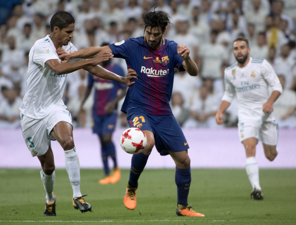 Real Madrid's French defender Raphael Varane (L) vies with Barcelona's Portuguese midfielder Andre Gomes during the second leg of the Spanish Supercup football match Real Madrid vs FC Barcelona at the Santiago Bernabeu stadium in Madrid, on August 16, 2017. / AFP PHOTO / CURTO DE LA TORRE