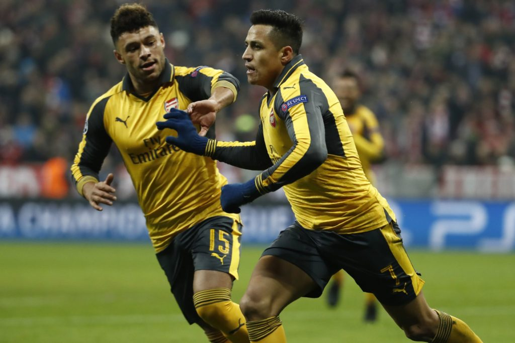 Arsenal's Chilean striker Alexis Sanchez (R) celebrates scoring the 1-1 goal with his teammate midfielder Alex Oxlade-Chamberlain during the UEFA Champions League round of sixteen football match between FC Bayern Munich and Arsenal in Munich, southern Germany, on February 15, 2017.  / AFP PHOTO / Odd ANDERSEN