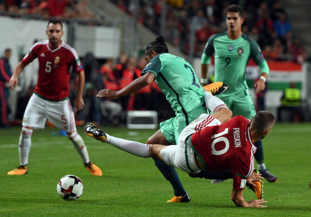 Portugal's Bruno Alves (C) vies with Hungary's Tamas Priskin (R) during the FIFA World Cup 2018 qualification football match between Hungary and Portugal in Budapest on September 3, 2017. / AFP PHOTO / ATTILA KISBENEDEK