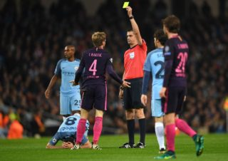 Hungarian referee Victor Kassai (3R) shows a yellow card to Barcelona's Croatian midfielder Ivan Rakitic (C) during the UEFA Champions League group C football match between Manchester City and Barcelona at the Etihad Stadium in Manchester, north west England on November 1, 2016. / AFP PHOTO / PAUL ELLIS