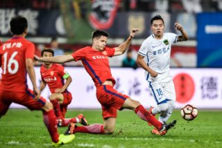 Hungarian football player Richard Guzmics, left, of Yanbian Funde kicks the ball to make a pass against a player of Guizhou Zhicheng in their 15th round match during the 2017 Chinese Football Association Super League (CSL) in Guiyang city, southwest China's Guizhou province, 2 July 2017.