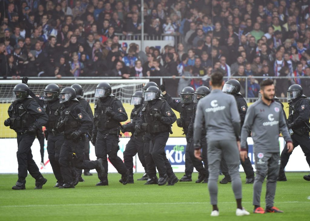 Police officers stand on the pitch prior to the German Second Bundesliga soccer match between Holstein Kiel and FC St. Pauli in the Holstein-Stadion in Kiel, Germany, 19 September 2017. Around 25 trouble makers ran on the pitch.  (EMBARGO CONDITIONS - ATTENTION: Due to the accreditation guidelines, the DFL only permits the publication and utilisation of up to 15 pictures per match on the internet and in online media during the match.) Photo: Axel Heimken/dpa