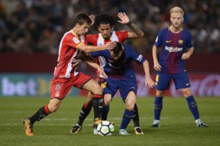 Barcelona's forward from Argentina Lionel Messi (C) vies with Girona's midfielder Pere Pons (L) and Girona's midfielder Alex Granell during the Spanish league football match Girona FC vs FC Barcelona at the Montilivi stadium in Girona on September 23, 2017. / AFP PHOTO / Josep LAGO