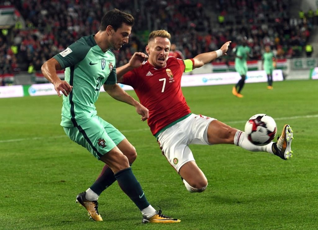 Portugal's Cedric (L) fights for the ball with Hungary's captain Balazs Dzsudzsak (R) during the FIFA World Cup 2018 qualification football match between Hungary and Portugal at The Grupama Arena in Budapest on September 3, 2017.   / AFP PHOTO / ATTILA KISBENEDEK