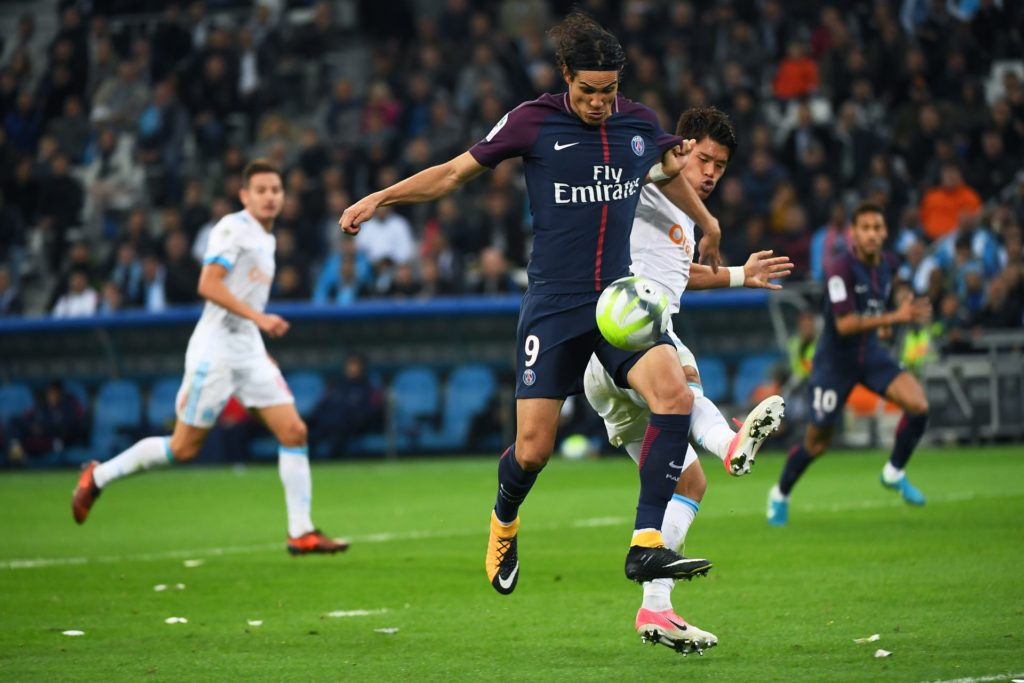 Paris Saint-Germain's Uruguayan forward Edinson Cavani (C) vies for the ball with Marseille's Japanese defender Hiroki Sakai  during the French L1 football match between Marseille (OM) and Paris Saint-Germain (PSG) on October 22, 2017, at the Velodrome Stadium in Marseille, southeastern France. / AFP PHOTO / ANNE-CHRISTINE POUJOULAT