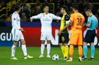 Real Madrid's forward from Wales Gareth Bale (L) and Real Madrid's forward from Portugal Cristiano Ronaldo (2nd L) argue with Dutch referee Bjorn Kuipers (R) after he gave Bale a yellow card during the UEFA Champions League Group H football match BVB Borussia Dortmund v Real Madrid in Dortmund, western Germany on September 26, 2017. / AFP PHOTO / Odd ANDERSEN
