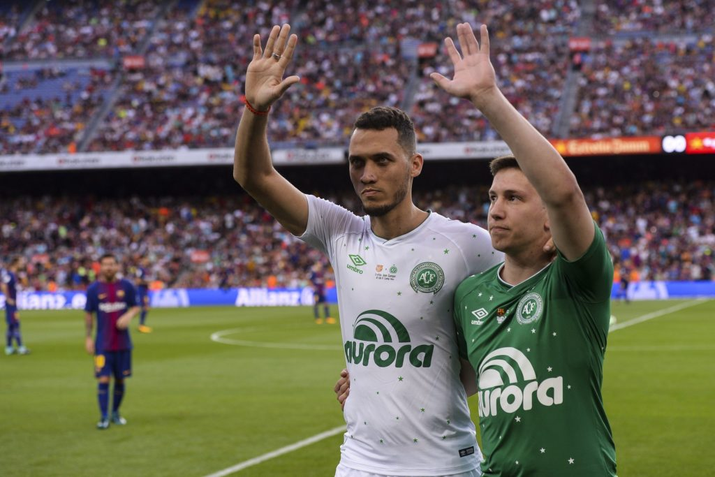 """Chapecoense's defender Neto (L) and Chapecoense's former goalkeeper Jakson Follmann wave to supporters after doing the honour kickoff before the 52nd Joan Gamper Trophy friendly football match between Barcelona FC and Chapecoense at the Camp Nou stadium in Barcelona on August 7, 2017. Funds raised from the match will """"help Chapecoense rebuild institutionally and recover the competitive level it had before the tragedy"""", Barca said in a statement as the Brazilian side still reeling from a devastating plane crash that killed 19 players and 24 club officials last year. / AFP PHOTO / Josep LAGO"""