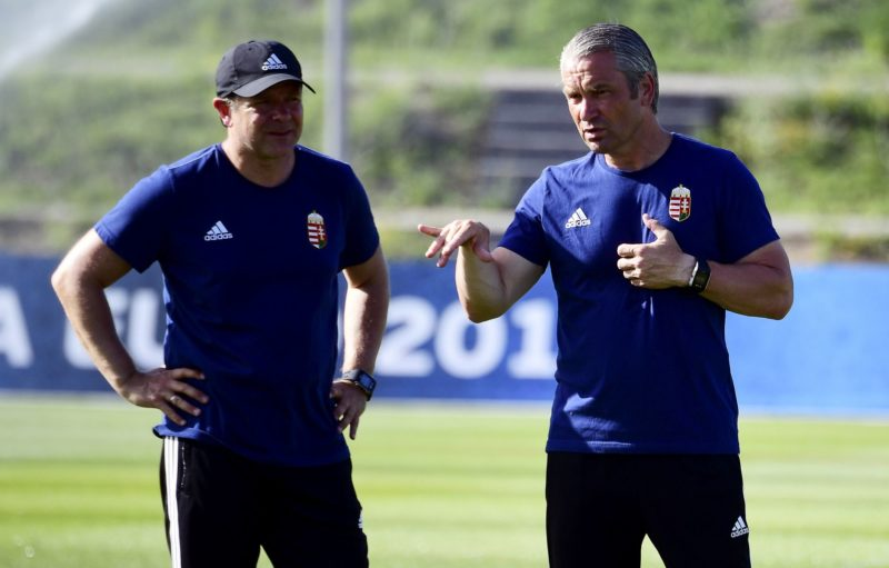 Hungary's  German head coach Bernd Storck (R) talks with his  German assistant coach Andreas Moller (L) prior to a training session in Tourrettes, southern France, on June 24, 2016, two days prior to their Euro 2016 round of 16 football match against Belgium.  / AFP PHOTO / ATTILA KISBENEDEK