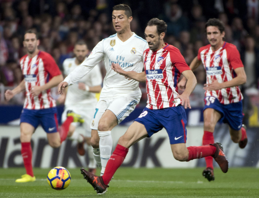 """Real Madrid's Portuguese forward Cristiano Ronaldo (L vies with Atletico Madrid's Spanish defender Juanfran during the Spanish league football match Atletico Madrid vs Real Madrid at the Wanda Metropolitan stadium in Madrid on November 18, 2017. / AFP PHOTO / CURTO DE LA TORRE / """"The erroneous byline appearing in the metadata of this photo by Curto DE LA TORRE has been modified in AFP systems in the following manner: [Curto de la Torre] instead of [Eduardo Dieguez]. Please immediately remove the erroneous mention[s] from all your online services and delete it (them) from your servers. If you have been authorized by AFP to distribute it (them) to third parties, please ensure that the same actions are carried out by them. Failure to promptly comply with these instructions will entail liability on your part for any continued or post notification usage. Therefore we thank you very much for all your attention and prompt action. We are sorry for the inconvenience this notification may cause and remain at your disposal for any further information you may require."""""""
