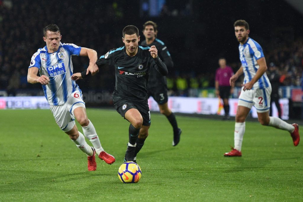 Huddersfield Town's English midfielder Jonathan Hogg (L) vies with Chelsea's Belgian midfielder Eden Hazard during the English Premier League football match between Huddersfield Town and Chelsea at the John Smith's stadium in Huddersfield, northern England on December 12, 2017. / AFP PHOTO / Oli SCARFF / RESTRICTED TO EDITORIAL USE. No use with unauthorized audio, video, data, fixture lists, club/league logos or 'live' services. Online in-match use limited to 75 images, no video emulation. No use in betting, games or single club/league/player publications.  /