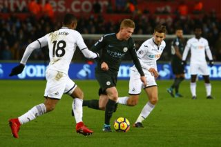 Manchester City's Belgian midfielder Kevin De Bruyne (C) vies with Swansea City's Ghanaian striker Jordan Ayew and Swansea City's English midfielder Tom Carroll (R) during the English Premier League football match between Swansea City and Manchester City at The Liberty Stadium in Swansea, south Wales on December 13, 2017. SW18MC17SW14 / AFP PHOTO / Geoff CADDICK / RESTRICTED TO EDITORIAL USE. No use with unauthorized audio, video, data, fixture lists, club/league logos or 'live' services. Online in-match use limited to 75 images, no video emulation. No use in betting, games or single club/league/player publications.  /