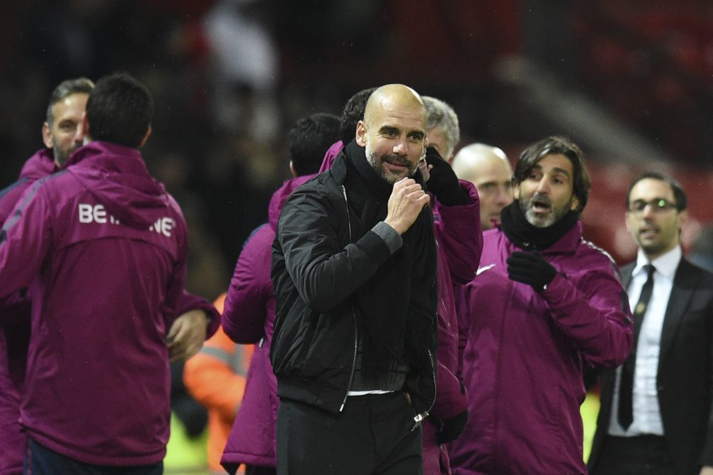Manchester City's Spanish manager Pep Guardiola (C) celebrates at the end of the English Premier League football match between Manchester United and Manchester City at Old Trafford in Manchester, north west England, on December 10, 2017. / AFP PHOTO / Oli SCARFF / RESTRICTED TO EDITORIAL USE. No use with unauthorized audio, video, data, fixture lists, club/league logos or 'live' services. Online in-match use limited to 75 images, no video emulation. No use in betting, games or single club/league/player publications.  /