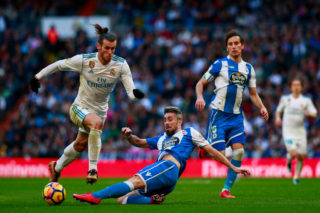 MADRID, SPAIN - JANUARY 21: Gareth Bale (L) of Real Madrid CF is tackled by Luisinho Correia (2ndR) Deportivo La Coruna  during the La Liga match between Real Madrid CF and Deportivo La Coruna at Estadio Santiago Bernabeu on January 21, 2018 in Madrid, Spain. (Photo by Gonzalo Arroyo Moreno/Getty Images)