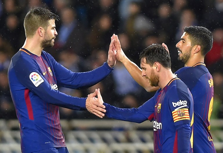 Barcelona's Uruguayan forward Luis Suarez (R) celebrates his second goal with Barcelona's Argentinian forward Lionel Messi (2R) and Barcelona's Spanish defender Gerard Pique during the Spanish league football match between Real Sociedad  and FC Barcelona at the Anoeta stadium in San Sebastian on January 14, 2018. / AFP PHOTO / ANDER GILLENEA