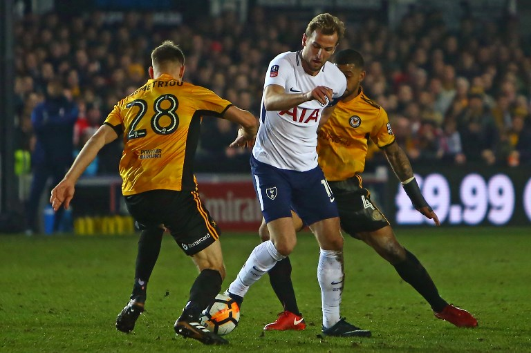 Tottenham Hotspur's English striker Harry Kane (C) vies with Newport County's English defender Mickey Demetriou (L) and Newport County's English midfielder Joss Labadie (R) during the English FA Cup fourth round football match between Newport County and Tottenham Hotspur at Rodney Parade in Newport, in south Wales, on January 27, 2018. / AFP PHOTO / Geoff CADDICK / RESTRICTED TO EDITORIAL USE. No use with unauthorized audio, video, data, fixture lists, club/league logos or 'live' services. Online in-match use limited to 75 images, no video emulation. No use in betting, games or single club/league/player publications.  /