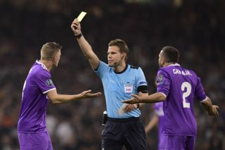 German referee Felix Brych shows a yellow card to Real Madrid's German midfielder Toni Kroos (L) during the UEFA Champions League final football match between Juventus and Real Madrid at The Principality Stadium in Cardiff, south Wales, on June 3, 2017. / AFP PHOTO / JAVIER SORIANO