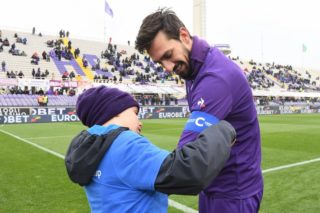 A boy gives the captain's armband to Fiorentina's player Davide Astori on February 25, 2018 before the Italian Seria A football match Fiorentina vs Chievo, in Florence. Italy international defender Davide Astori was found dead in his hotel room on March 4, 2018 in Udine, where he was due to play a Serie A game between Udinese and Fiorentina.  / AFP PHOTO / Claudio GIOVANNINI